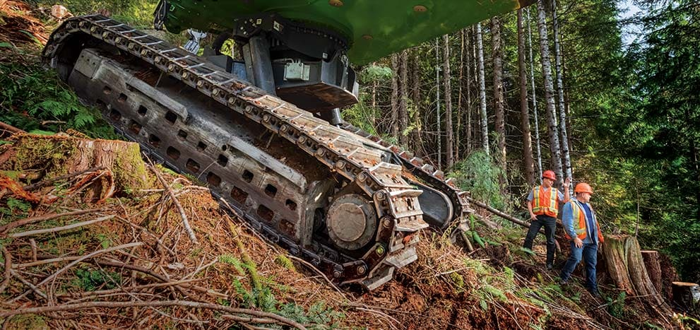 Tracks of a John Deere machine on a steep slope with loggers discussing the operation in the background