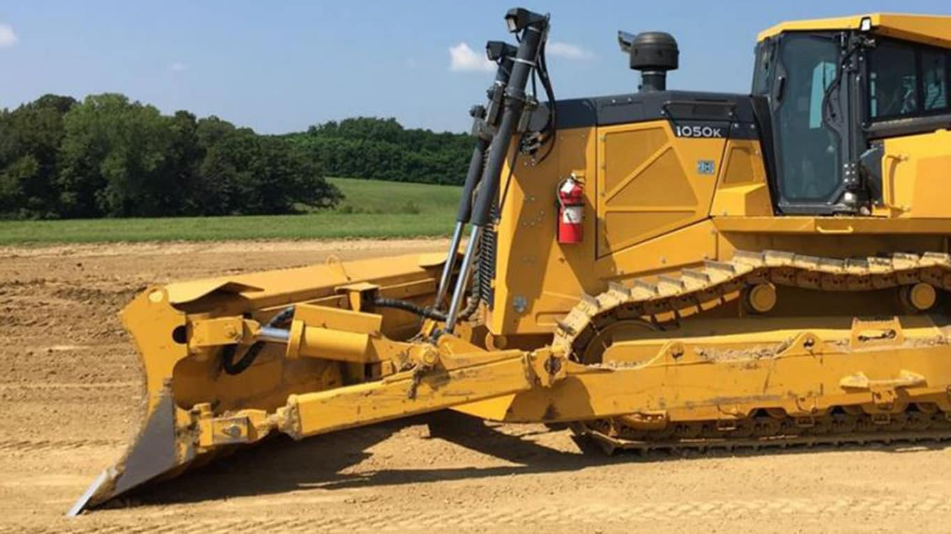 Close-up image of a 1050K Dozer with mechanical angle blade in the dirt