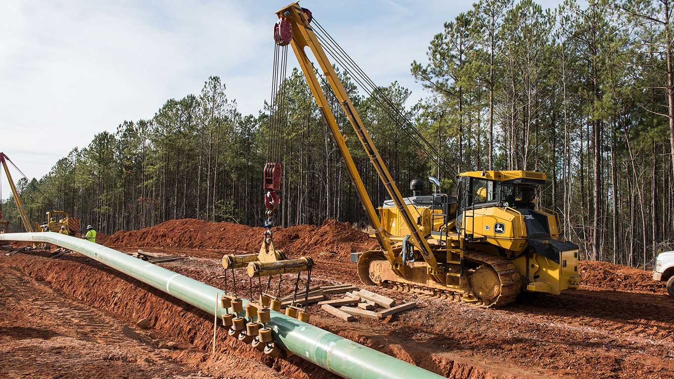 1050K Pipeline-Ready Dozer with side boom and winch moving a pipe