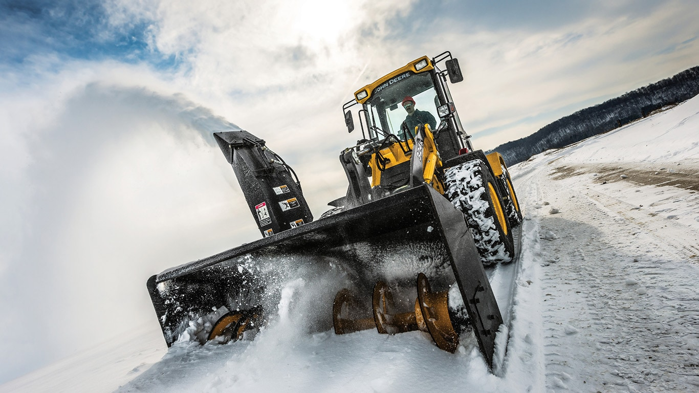 A John Deere Compact wheel loader with snowblower attachment working