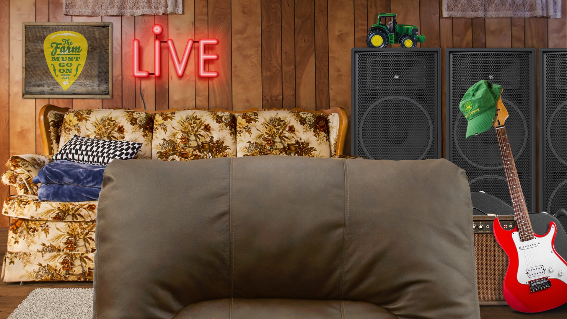 Rec room with chair back, concert poster, Live neon sign, sofa, guitar and speakers.