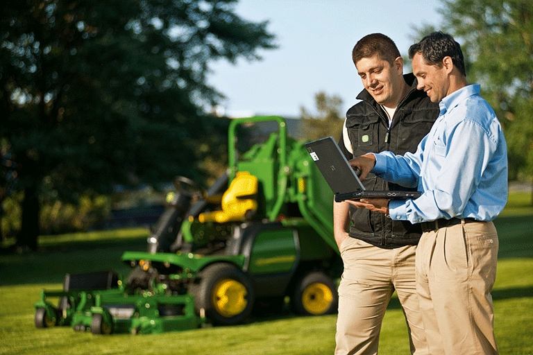 Two men talking while looking at a laptop with a John Deere mower in the background.