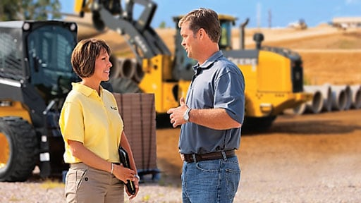 A woman and man have a conversation against a backdrop of construction equipment