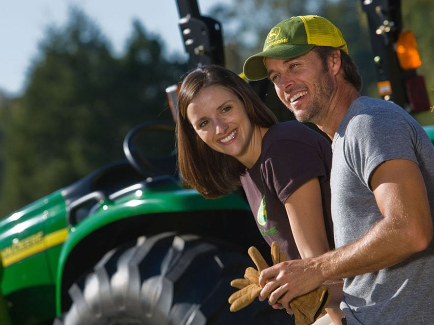 A young couple looks on with a tractor in the background