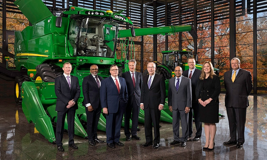 The John Deere leadership team stands at corporate headquarters with a tractor in the background