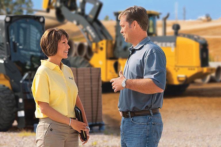 A man and a woman talking in front of a construction site with John Deere equipment.