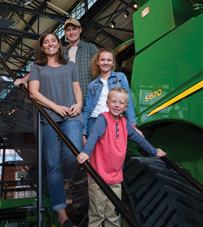 A family of four poses in front of a combine at the John Deere Pavilion