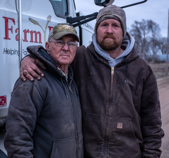 One man with his arm around another in front of a Farm semi truck