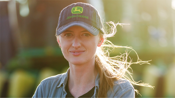 Woman smiling in John Deere baseball cap