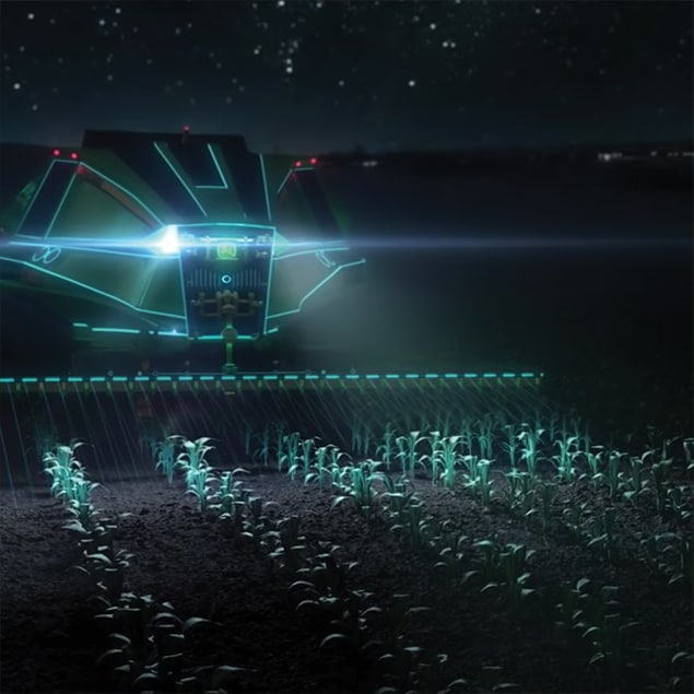 Futuristic John Deere machine fertilizing crops at night