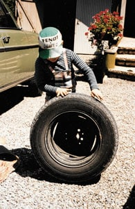 A young Martin Kremmer holds a tire while wearing a Fendt logo hat.