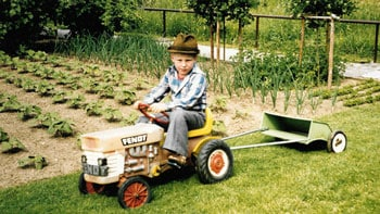 Child driving a toy lawn mower in the grass with garden in background.