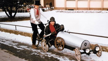 Two teens riding a vehicle they made for a parade.