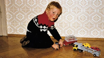 Boy plays on hardwood floor with toy trucks.