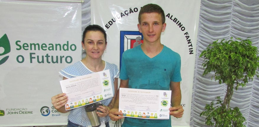 Aguila and Alex display holding certificates