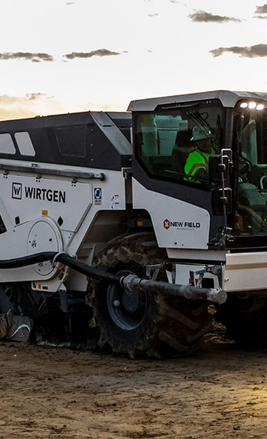 On a road building site, the following machines are lined up behind each other; Wirtgen cold recycler, John Deere crawler dozer, Wirtgen soil stabilizer and a John Deere motor grader