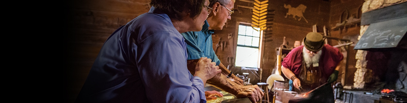 Older couple watching the blacksmith a piece of metal hammer at the Historic Site in Grand Detour, Illinois, United States