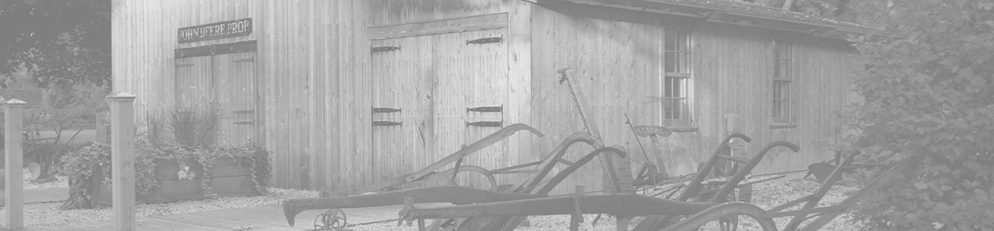 Toned black and white photograph of the Historic Site's recreation of John Deere's original blacksmith shop on a green background
