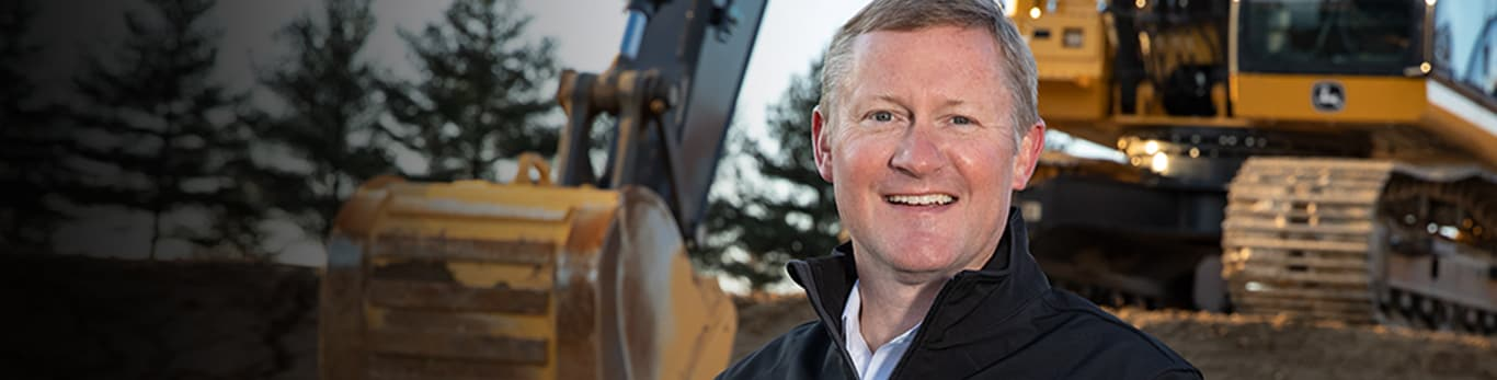 CEO and Chairman John May standing in front of a John Deere excavator at a construction site