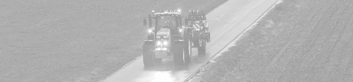 Toned black and white photograph of a 6M Series tractor on a road with its lights on transporting a cultivator on a green background