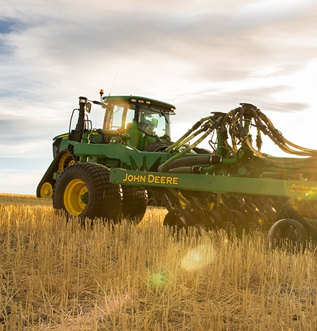 A John Deere 9RX Series Tractor using a No-Till Air Drill planter in Montana, United States wheat field