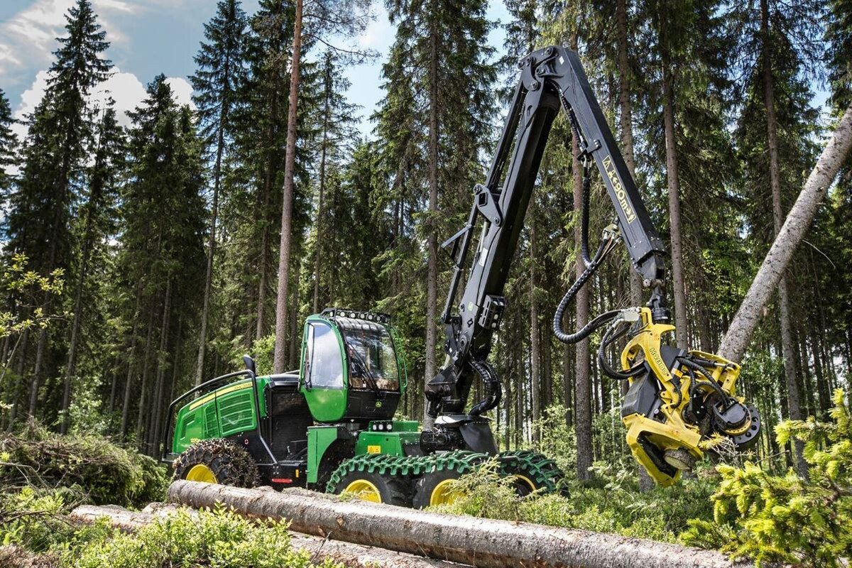 The John Deere 1270G wheeled harvester lifting a log in the forest.