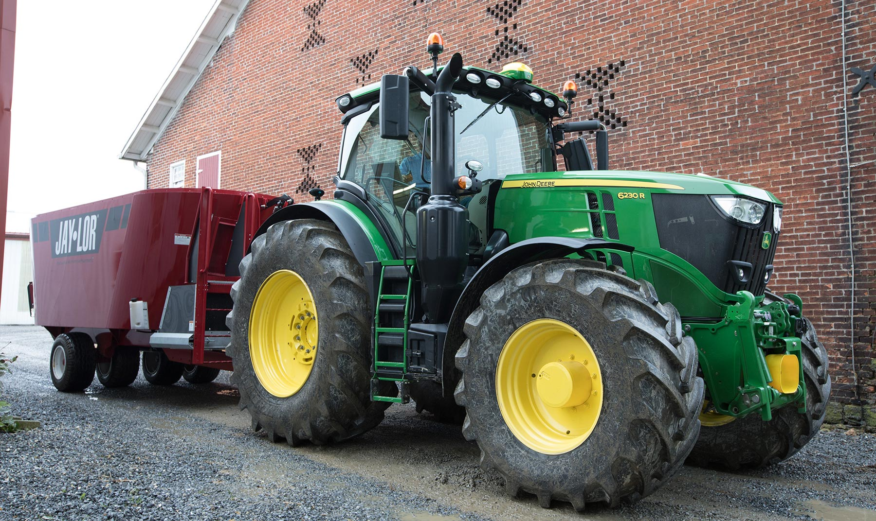 A 6230R tractor parked by a building
