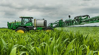 Side view of a John Deere sprayer with new row guidance product working in a field of corn