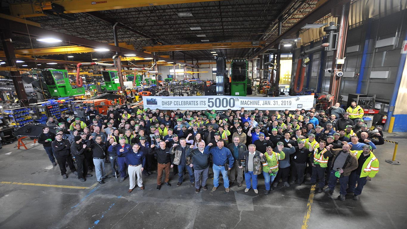 Group photo of Deere-Hitachi Specialty Products factory employees and Bighorn Logging in front of 2656G Swing Machine.