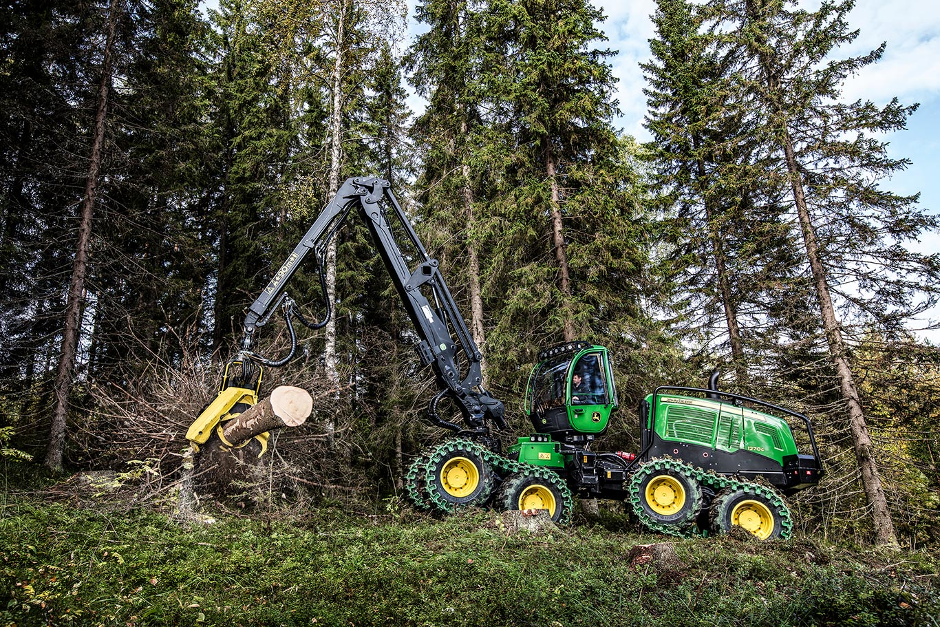 The John Deere 1270G wheeled harvester felling a tree at a jobsite.