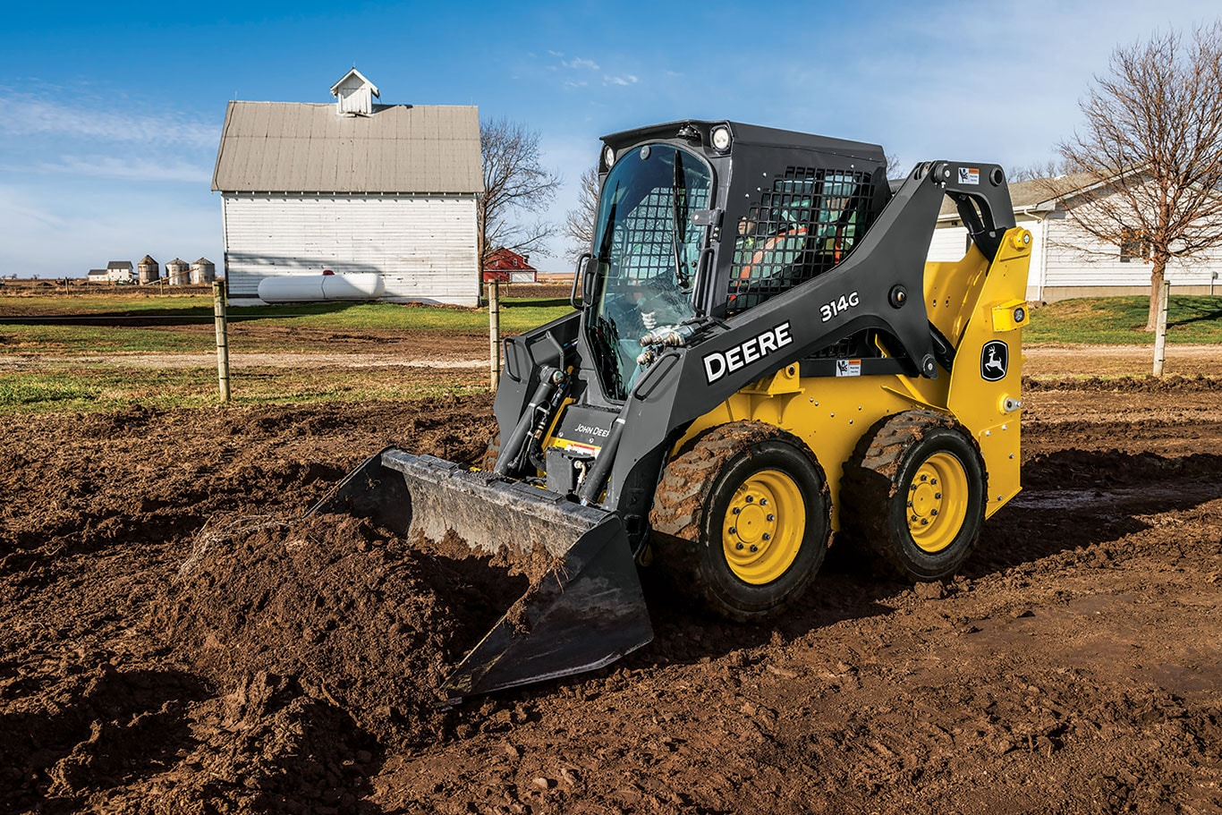 John Deere Skid Steer pushing dirt at a construction site.