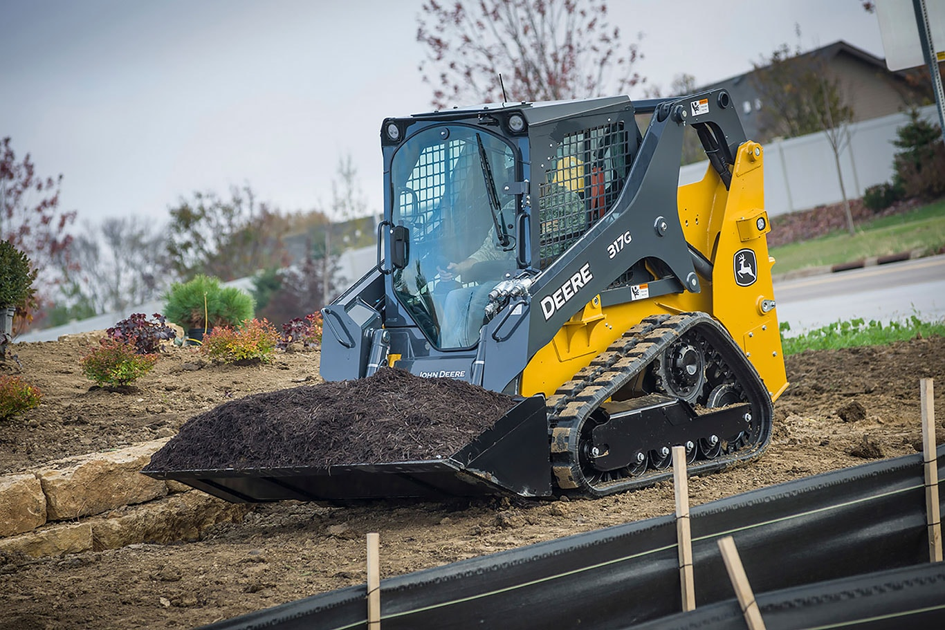 John Deere compact track loader hauling a bucketful of dirt at a jobsite
