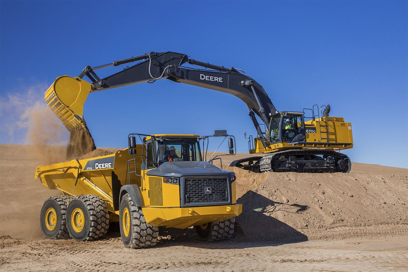 670G LC excavator dumbs a load of dirt into an articulated dump truck