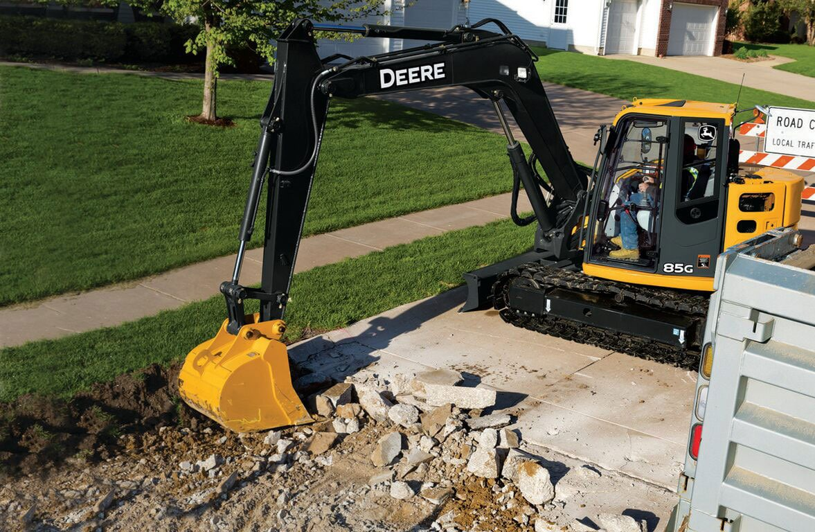 A Deere 85g excavator working on a residential street