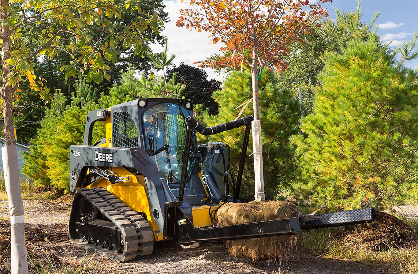 The John Deere 329E Skid Steer with the Nursery Fork attachment moves a tree