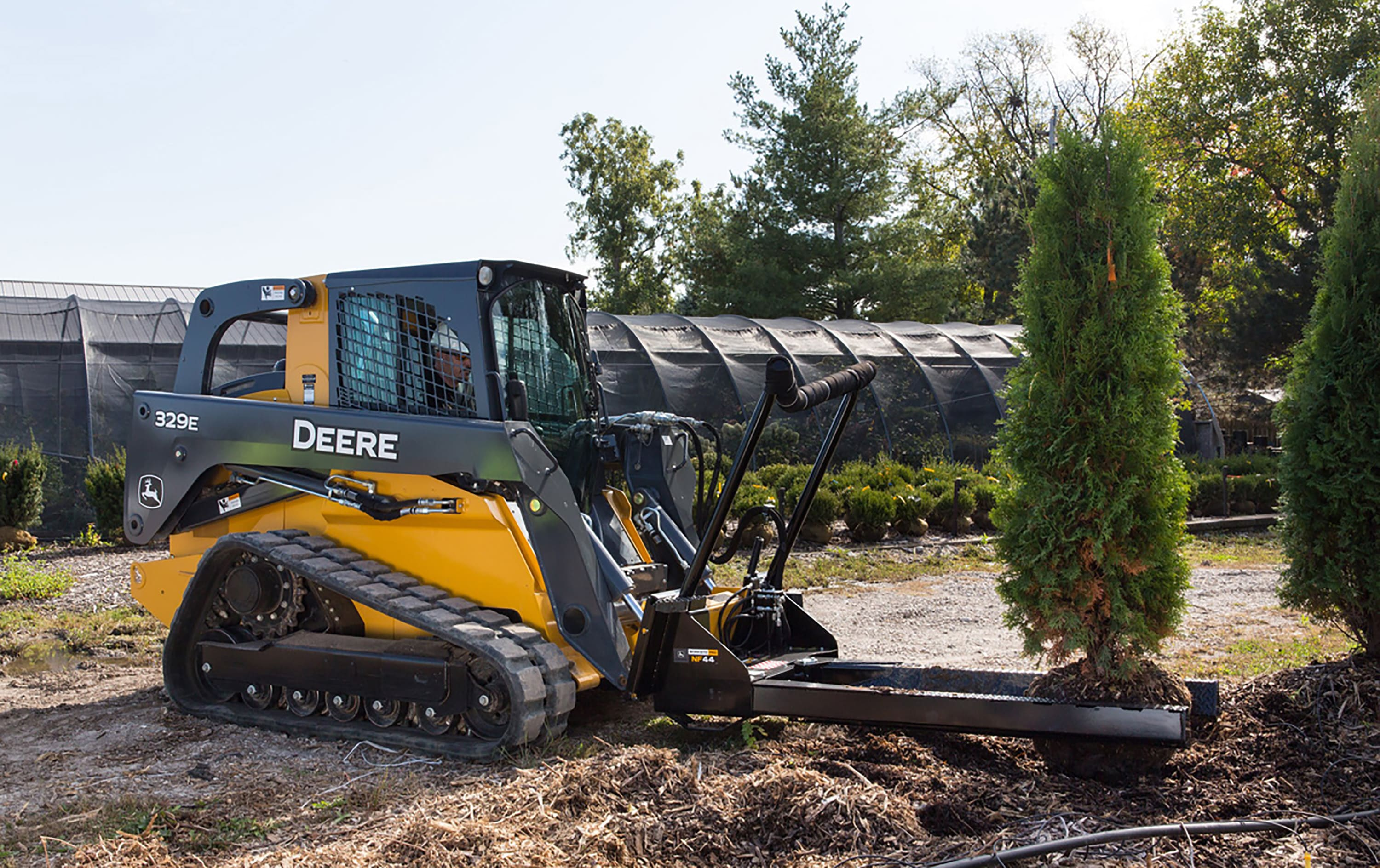 The John Deere 329E Skid Steer with the Nursery Fork attachment approaches a tree to transport