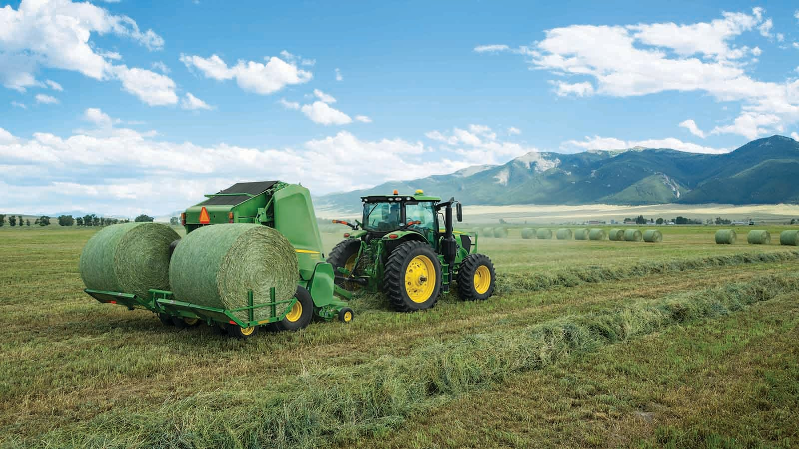 A John Deere 560M Round Baler equipped with a new A520R Plus2 Accumulator  carries up to