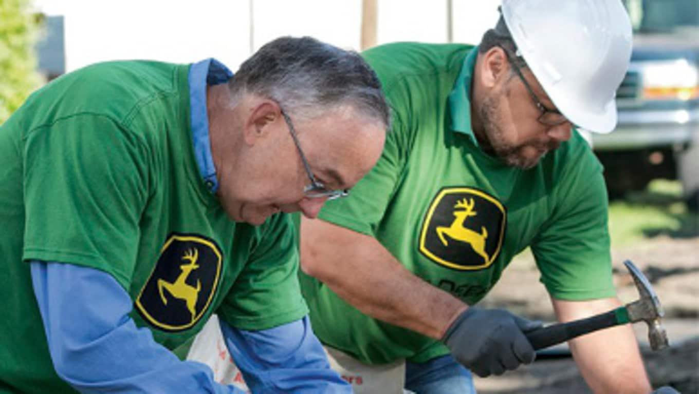 John Deere CEO Sam Allen and another Deere employee working at a volunteer event