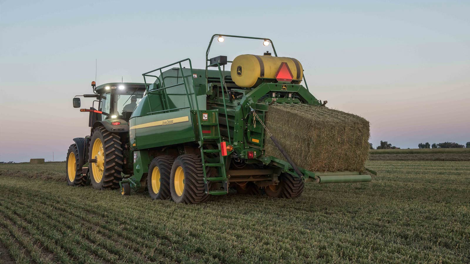 John Deere tractor with a large square baler attached