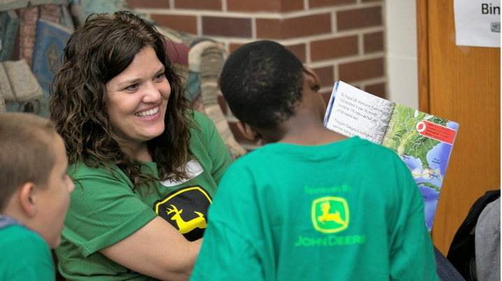 John Deere employee smiles as she reads book to children.