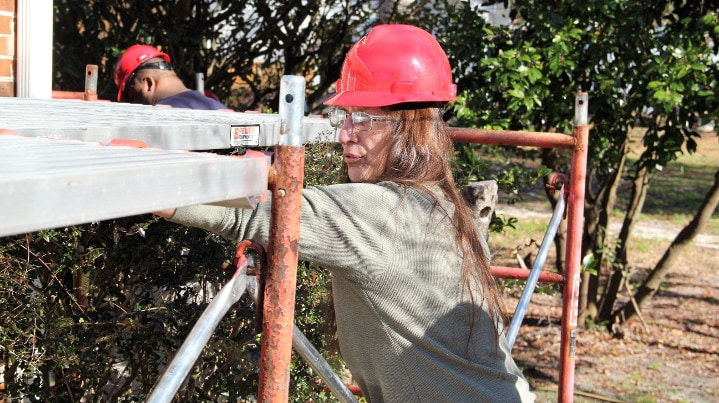 Woman wears hard-hat and safety glasses working near scaffolding.