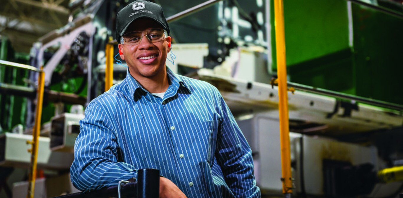Smiling John Deere factory worker posing in front of manufacturing equipment in the factory