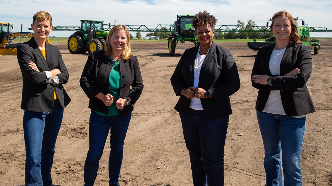 four female managers in front of equipment