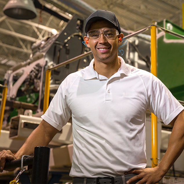 Hispanic man wearing protective eye wear and ear protection standing in beside a combine
