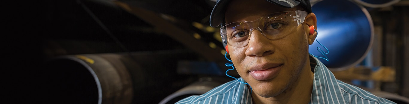 African-American man wearing protective eye wear and ear protection looks on