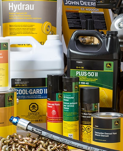 Group of John Deere coolants, paints, cleaners, chemicals, greases, oils, chains, and hydraulic hoses sitting on top of workshop bench
