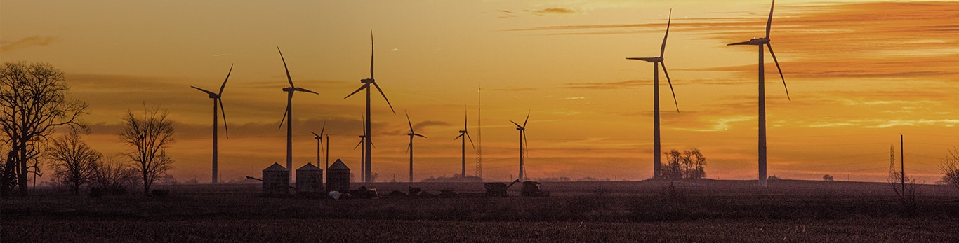A silhouettes of wind turbines on farm land with a beautiful orange sunset behind them in Indiana, United States.