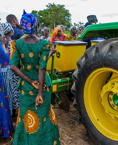 Women farmers in northern Ghana are gathered around a John Deere planter to learn about mechanized farming at a TechnoServe event.