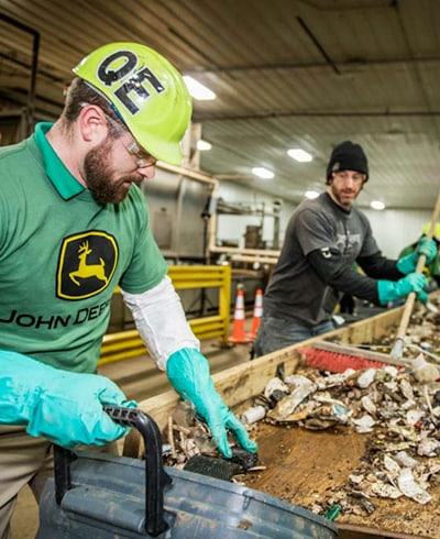 John Deere employees from  Gator Works factory in Horicon, Wisconsin volunteering at a local recycling center by sorting plastics.