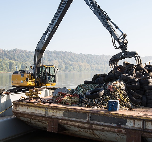 John Deere 210G LC with a grapple loading old tires onto a barge to be shipped to a recycling plant.